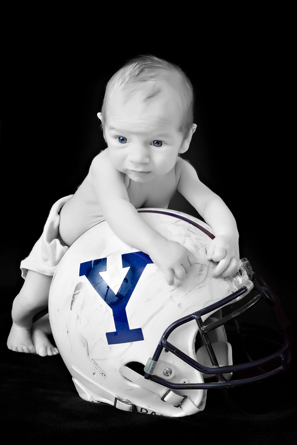 Portrait of Baby on Yale Football Helmet on Black Background in the Studio