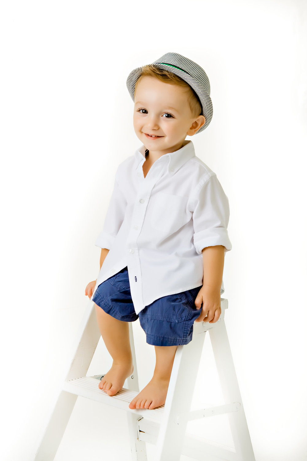 Portrait of a young boy sitting on a ladder on a white background