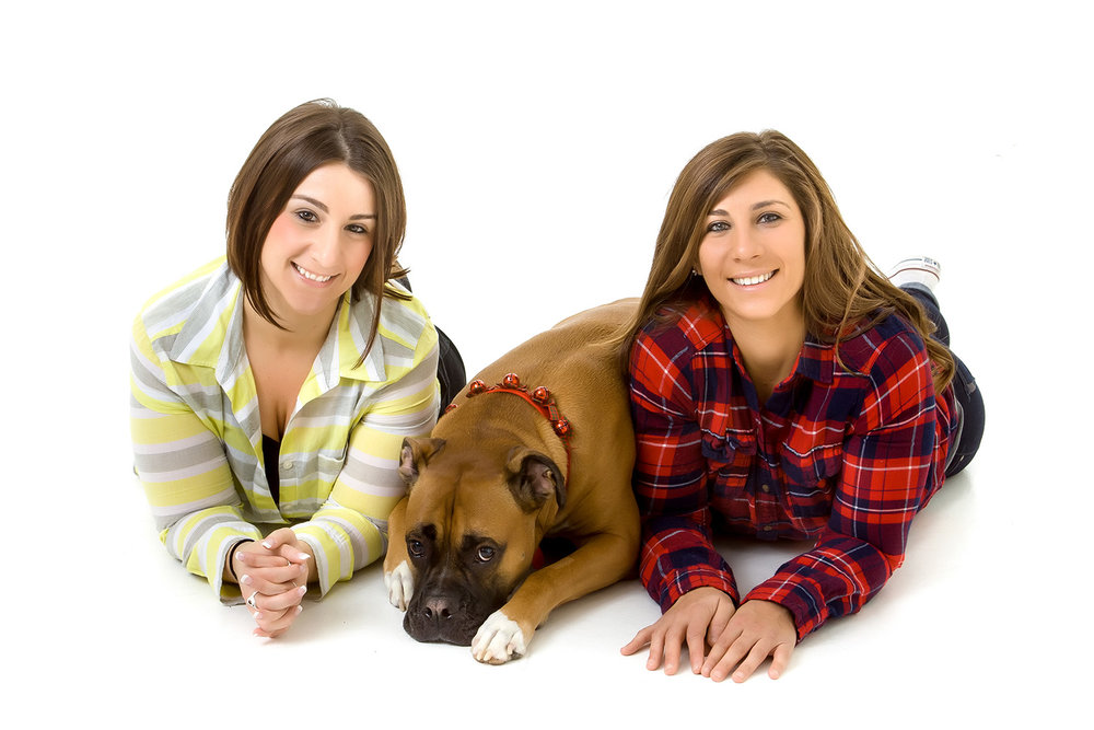 Casual Portrait of two young woman with their dog on a white background