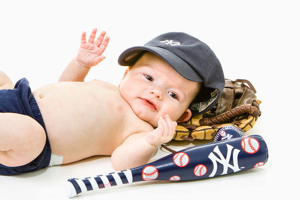 Portrait of baby with a yankee hat mit and baseball bat