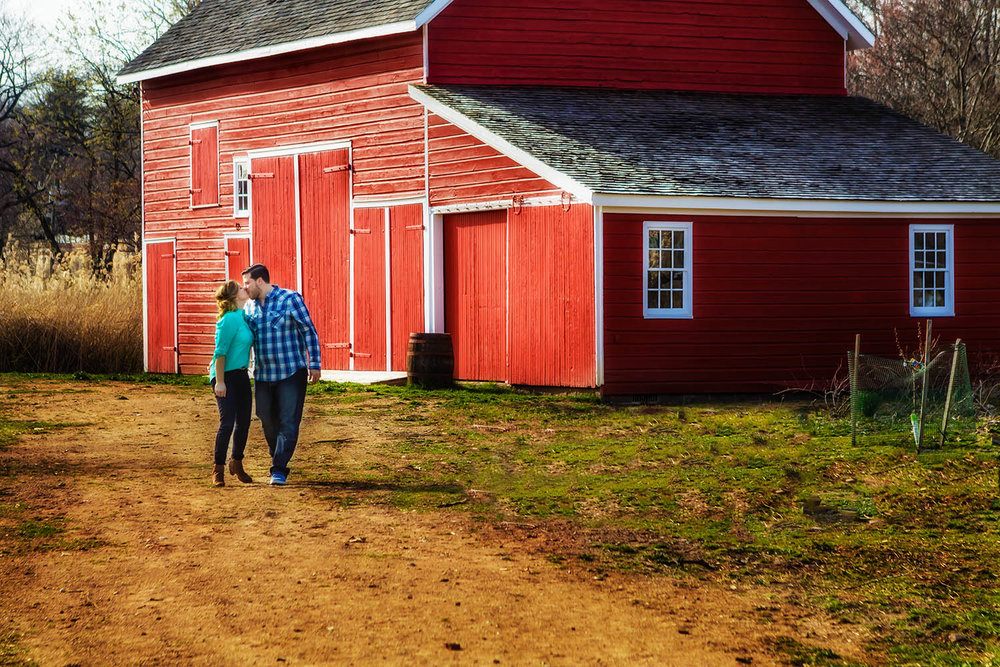 Engagement photography in river edge in front of a red barn