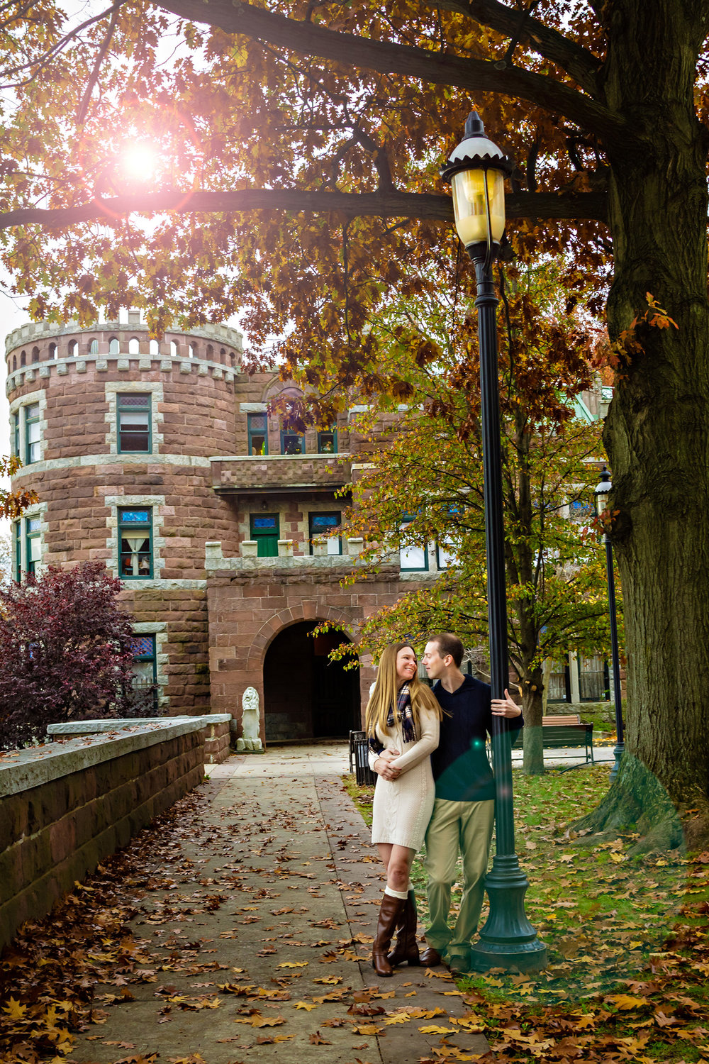 Photos of an engaged couple by the lamp post at Lambert Castle in Paterson