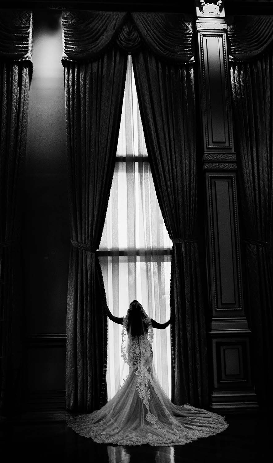 Silhouette of a Bride in front of the Large windows in the ballroom at the tides estates in north haledon nj in black and white