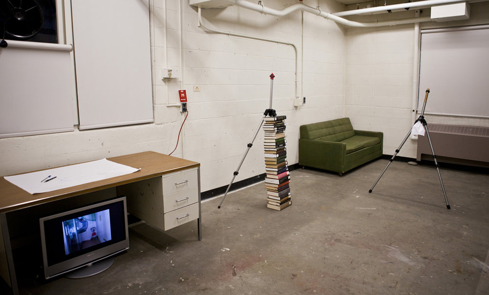 aluminum tripod, book, latex condom, working table, digital monitor, single channel video (Installation view)
