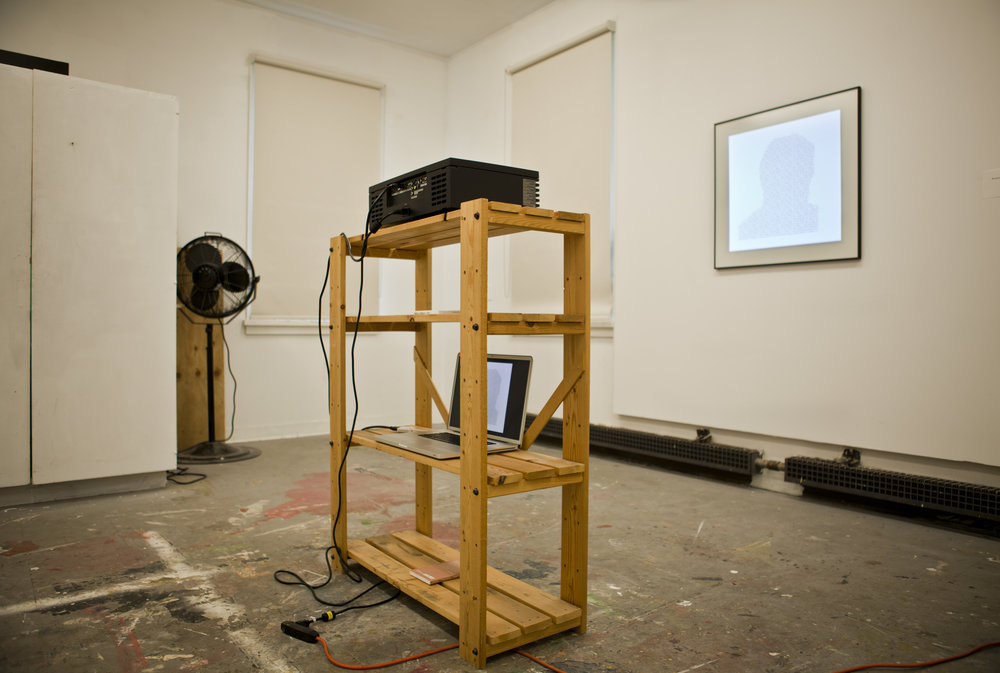 """Installation view: Wooden shelf, HD Projector, Apple Care Package,17"""" McBook Pro,Book, Empty frame, Glass, HD text projection."""