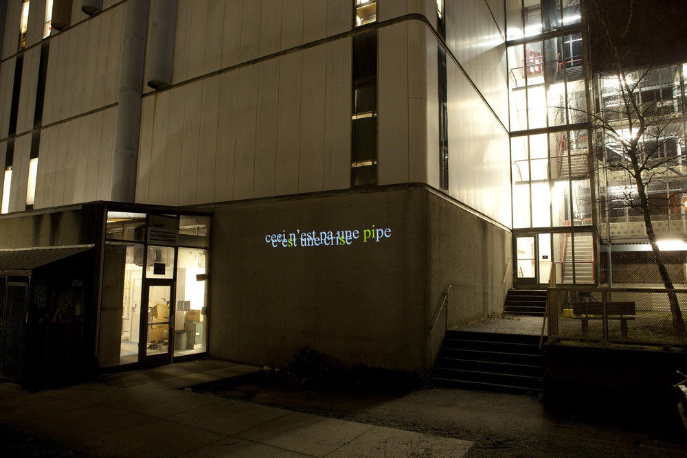 "HD Text projection onto UBC's Power building. ""Ceci n'est pas une  pi pe C'e s t une cri s e"""