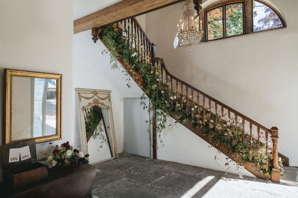 Outdoor wedding at Pennard House, Somerset_staircase decorated with garden flowers