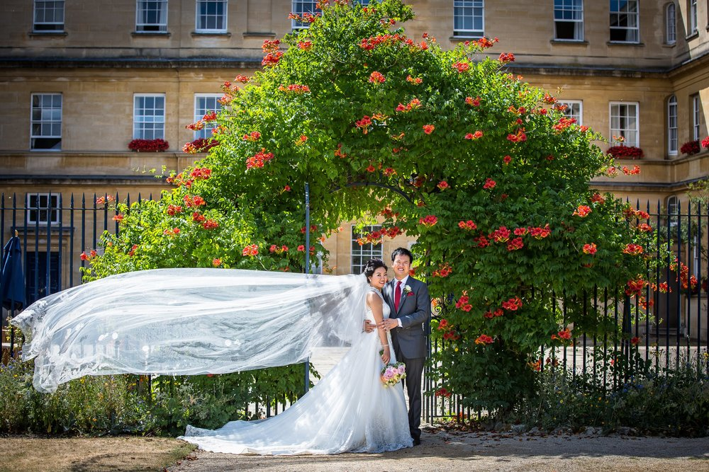 Oxford college wedding_couple pose beneath floral arch