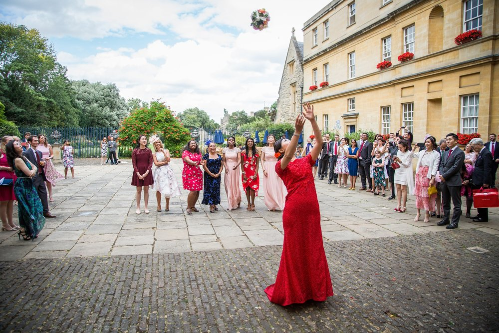 Oxford college wedding_brides wears traditional Chinese dress and throws bouquet