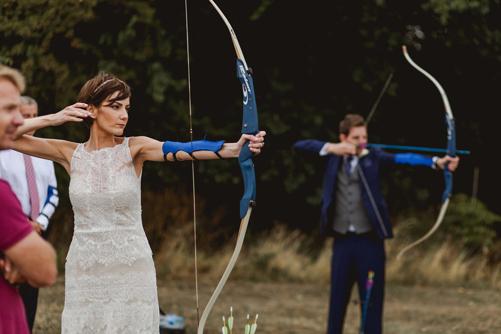 Eggington House marquee wedding_bride and groom try archery
