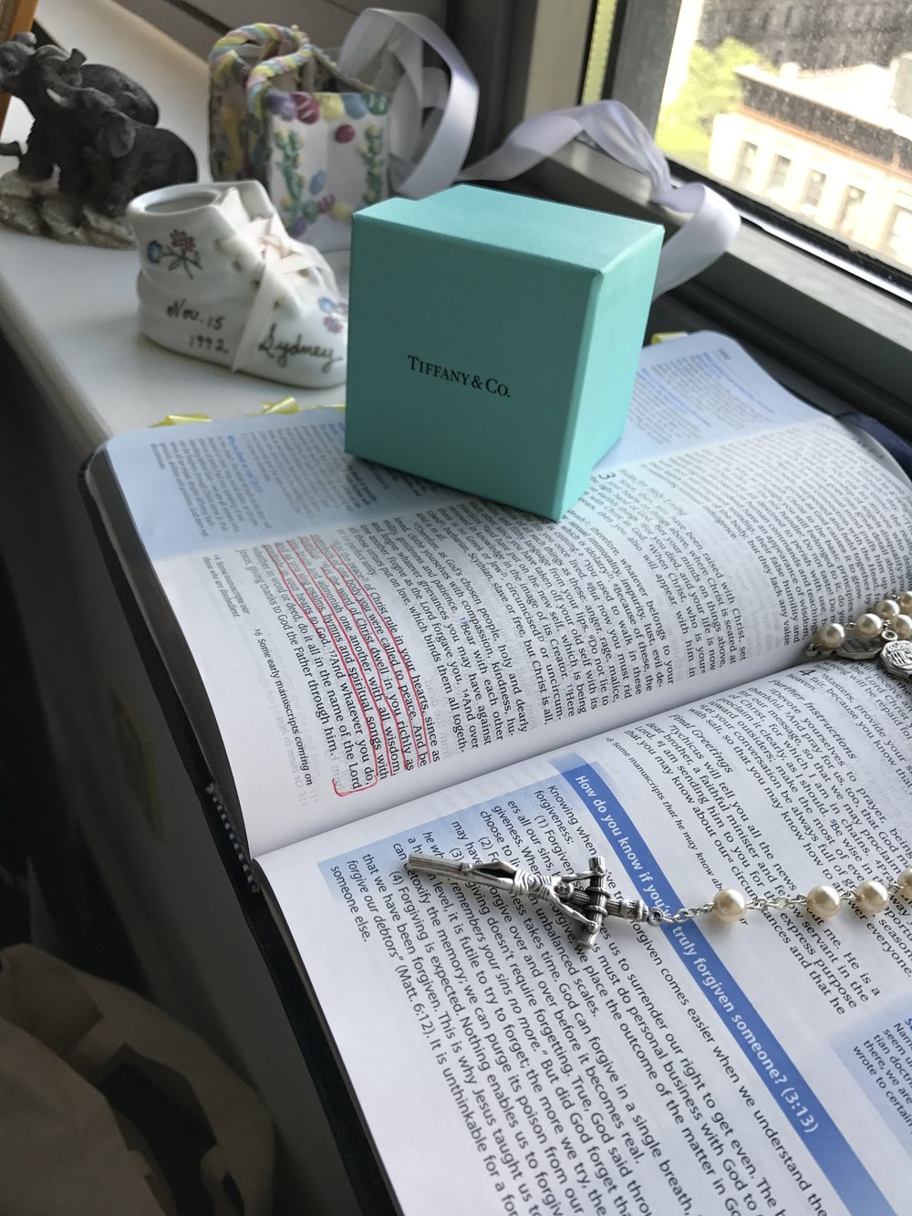 In the foreground is my Rosary, laid atop my Bible with our wedding verses underlined in red. Beyond that, our wedding bands from Tiffany + Co. Further still is the little ceramic shoe gifted to my parents upon my birth, with my name, birthdate, weight and length on it.