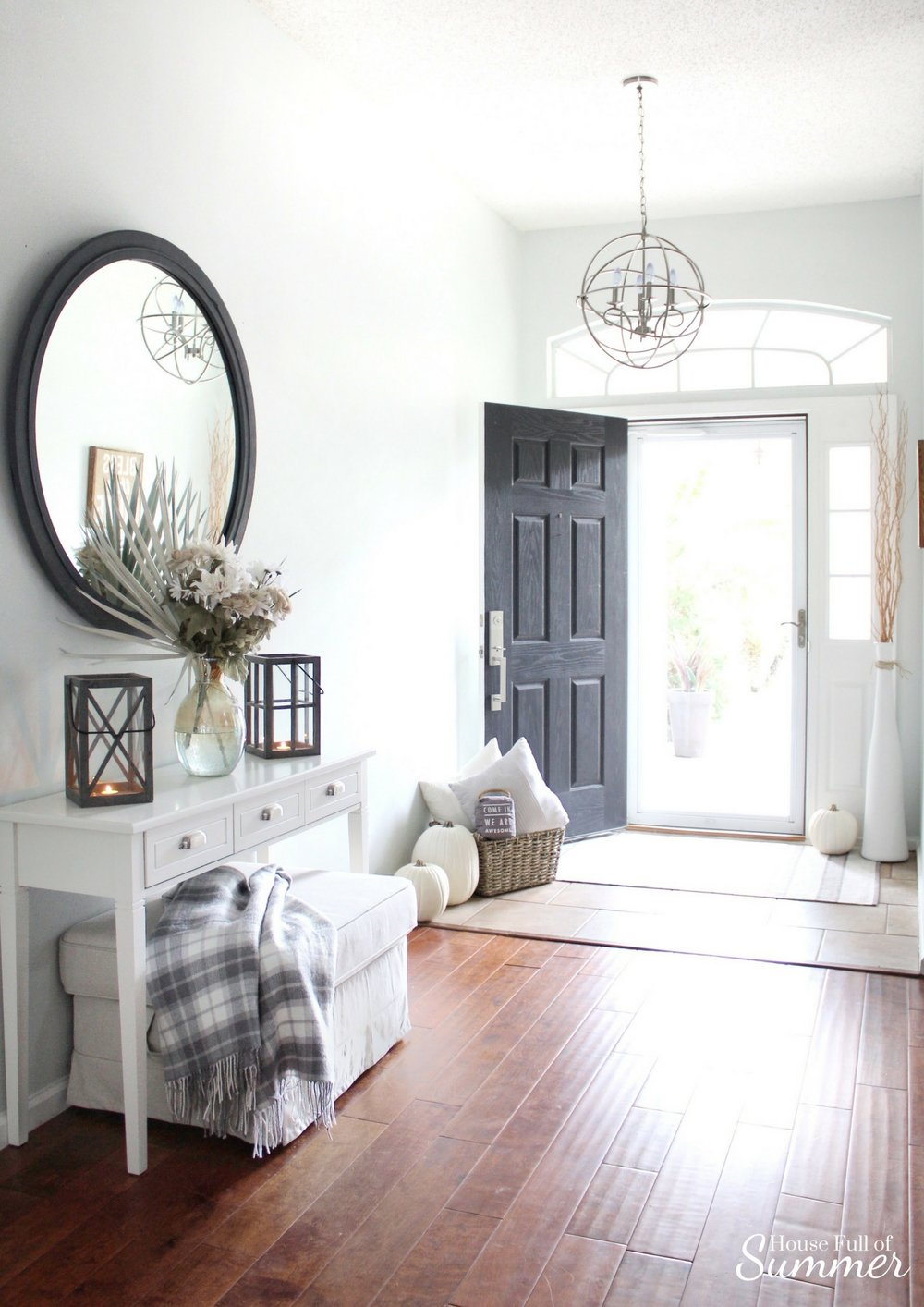 House Full of Summer: Fall Home Tour Blog Hop - Cozy, Coastal, Chic Foyer fall decorating ideas. Neutral interior, white pumpkins, front door decor, white console table, plaid throw, faux fall florals, entryway, wood floors, front door color, orb chandelier, round mirror, lanterns, ottoman