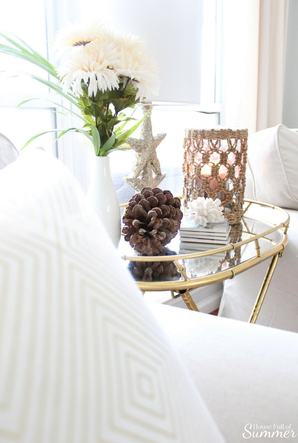 House Full of Summer: Fall Home Tour Blog Hop - Cozy, Coastal, Chic Living Room fall decorating ideas. Neutral interior, living room decor, gold bamboo folding table, mirrored side table, throw pillow covers, faux fall florals, living room ideas, sitting room, wood floors, table styling, pine cones, gold accents