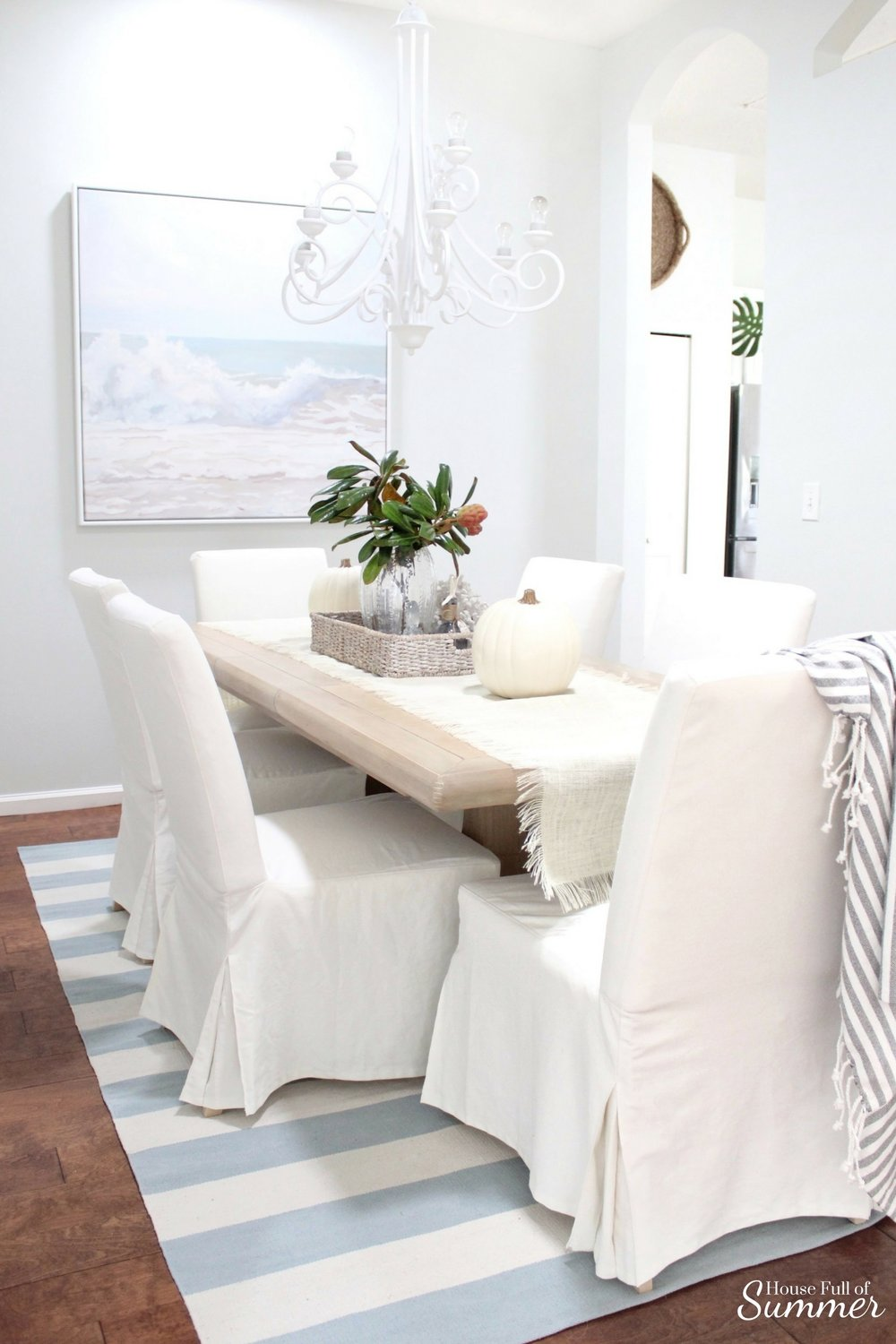 House Full of Summer: Fall Home Tour Blog Hop - Cozy, Coastal, Chic  Dining Room, pottery barn style, beachy decor, white slipcovered chairs, ocean beach painting, striped rug, flat weave, table runner, fall table ideas, ballard designs, ikea chairs, centerpiece, white pumpkins, neutral fall decor