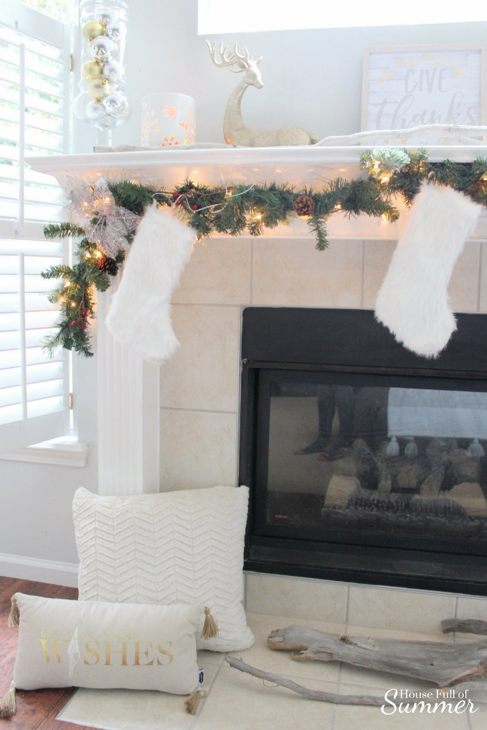 Classy Christmas Home Tour {Part Two} | House Full of Summer blog - mantel decor, christmas mantel ideas, coastal christmas mantel, silver and gold coastal decor, windows over mantel, white fur stockings, gold reindeer, driftwood, coastal home ideas
