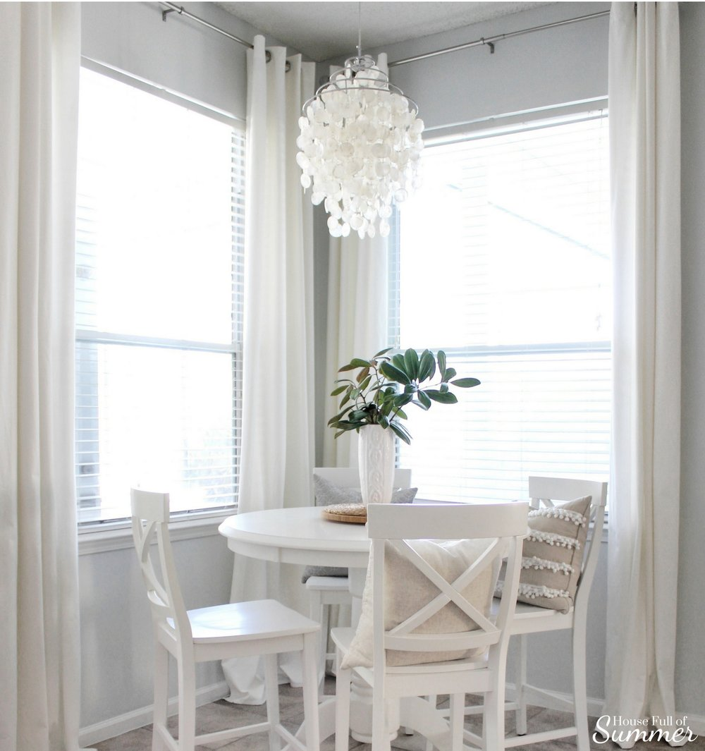 Add New Life to Your Home With This New Year's Resolution | House Full of Summer blog adding greenery to your home, decorating with plants, fronds, trimmings, winter decor, home decor, coastal home, magnolia centerpiece, white breakfast nook, counterheight table and chairs, capiz shell chandelier, extra long white curtains
