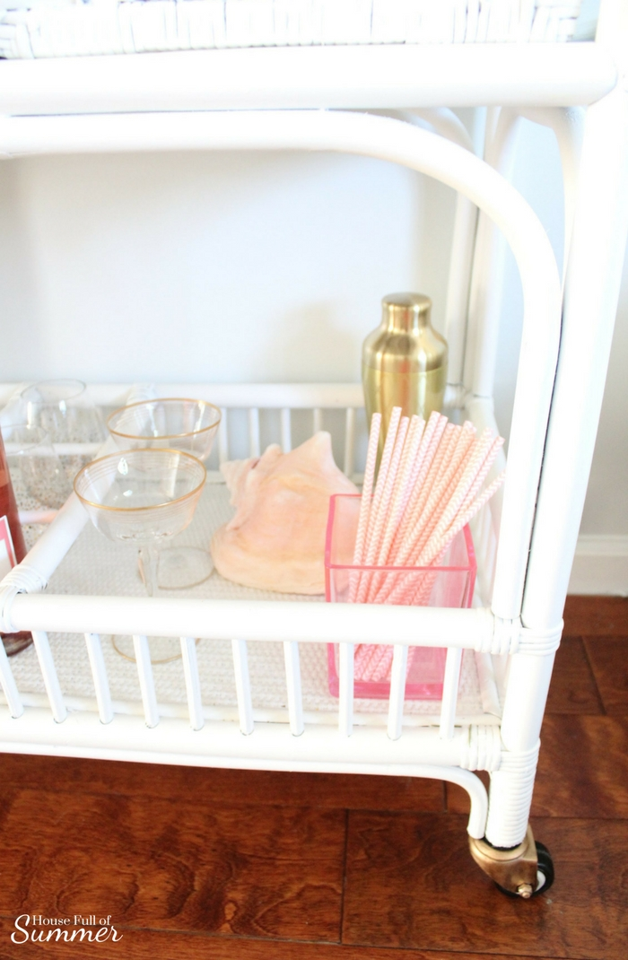 Blush Valentine's Day Cart With a Coastal Touch | House Full of Summer blog white cane bar cart, coastal bar cart styling, pink and gold valentine's day decor, tropical style, coastal home decor, framed sea fan, blush flowers, tray styling, cotton candy rose champagne cocktail drink