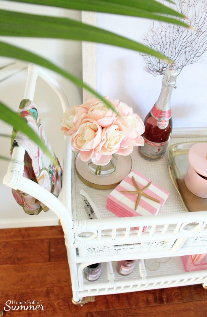 Blush Valentine's Day Cart With a Coastal Touch | House Full of Summer blog white cane bar cart, coastal bar cart styling, pink and gold valentine's day decor, tropical style, coastal home decor, framed sea fan, blush flowers, tray styling, cotton candy rose champagne cocktail drink vintage gold rimmed glasses