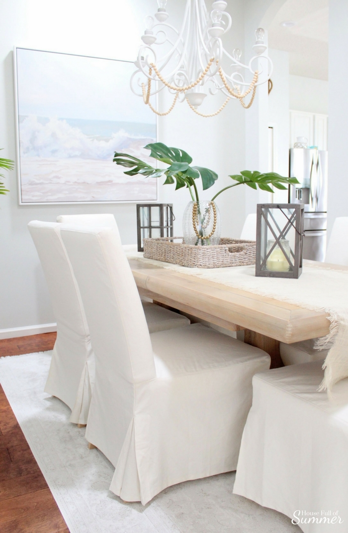 Why I Love My White Slipcovered Dining Chairs! | House Full of Summer - These IKEA chairs are the best bang for your buck and super comfortable! I'm telling you everything you need to know about them! Coastal dining room decor, faded fringe rug, vintage look rug, home decor on a budget, get the look for less, beachy boho dining room, tropical style, beaded chandelier DIY, palm fronds, ocean beach wall art.