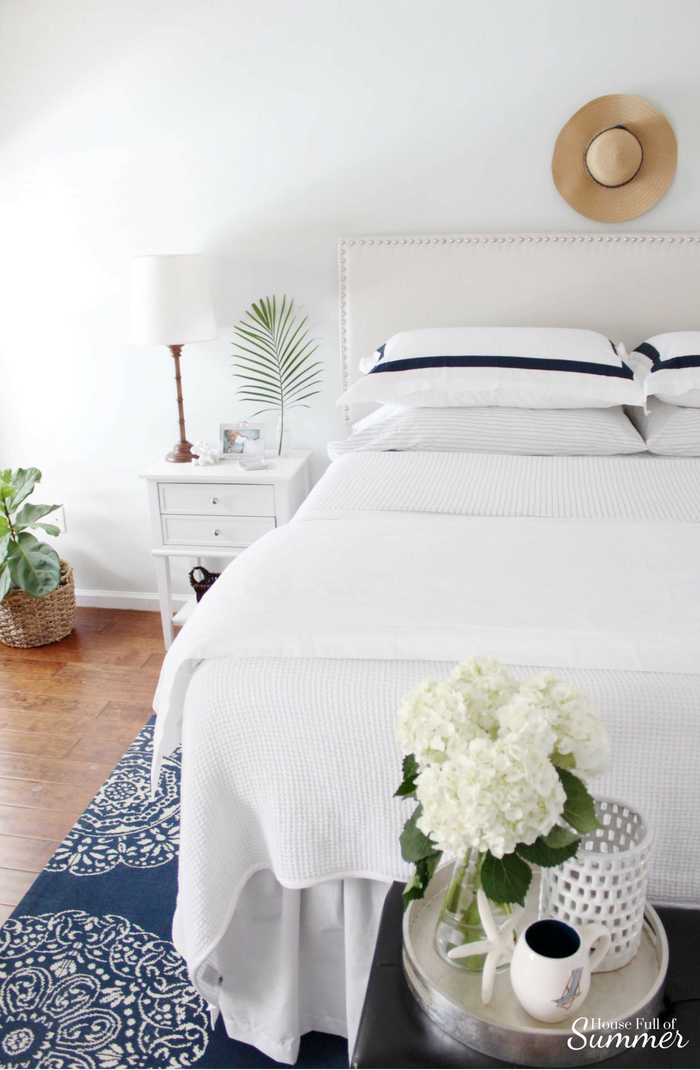 Casual Coastal Summer Bedding | House Full of Summer - nautical and coastal vibes in a blue and white bedroom. Boll & Branch duvet and navy ticking sheets, hotel bedding, beige nailhead headboard upholstered, extra long drop bed skirt, bamboo lamps, tropical accents, navy medallion rug. Sherwin Williams Fleur de Sel paint color, chinoiserie chic, cottage style