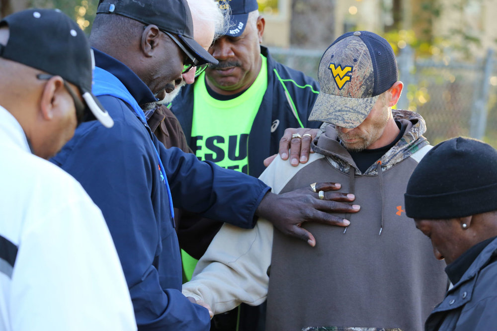 Billy Sloan  holds his hand to passerby Jason Sadler's heart while praying for recovering addicts. Thursday, Oct. 26, in Huntington, West Virginia. ( The Herald-Dispatch )