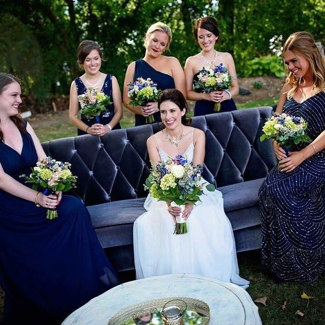 A seating vignette can create a cozy atmosphere for guests to relax with a drink and also makes a great photo op!  Doesn't our  beautiful bride and her bridal party look just perfect seated on our purple velvet sofa?  #weddingphotography #weddingrental #seatingvignette #vintagewedding#weddingideasweddinginspiration #outdoorwedding