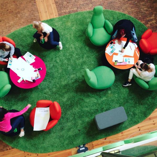 Syntolkning: Bilden är tagen under en workshop om Rättighetsreportrarna. Elever sitter i gröna och orangea fåtöljer på en stor grön matta. På borden framför sig har de papper, pennor, mobiltelefoner med mer.
