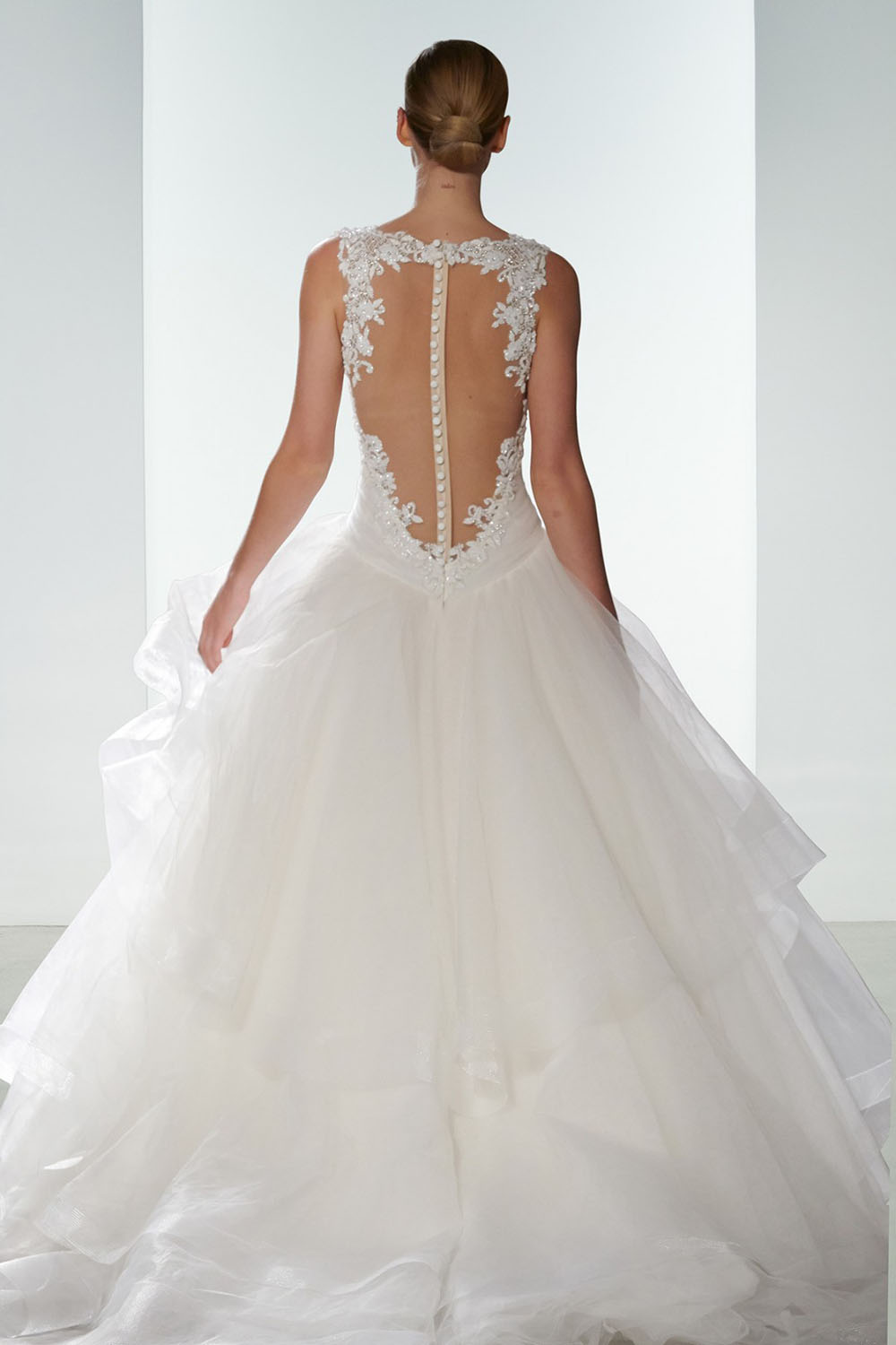 Season: Spring 2016    Gown name: Polina    Description: A sheer back ball gown with floral hand beaded bodice and layered tulle skirt.
