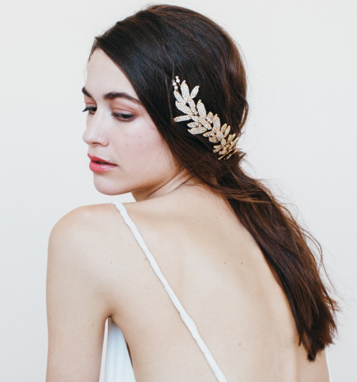 Name: ARIELLE CHIGNON WRAP WITH DOUBLE COMB    Description: The classic Jennifer Behr leaf motif, in a versatile and easy-to-wear comb. Lauren Conrad wore this hair accessory for her wedding, and Brea Larson wore it to the Oscars. Lauren wore it near the back of her head paired with a veil for the ceremony, then removed the veil for the reception. This hair accessory is the perfect show-stopping headpiece to complete your wedding hairstyle, and it is great for transitioning from the ceremony to a celebratory reception. Each Swarovski crystal is set by hand in New York City, taking hours of handwork. These crystal leaves are arranged on a flexible wire that can be carefully formed to fit around a chignon. Other celebrities that have worn this piece include Khloe Kardashian and Maggie Gyllenhaal. The comb is 4.5 inches long and has two petite combs to guarantee security in the hair. All Jennifer Behr hair accessories and headbands are handmade in New York City.