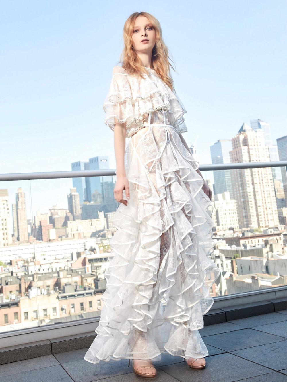 Season: Fall 2017    Gown name: Alberta 圆领领口合身剪裁的婚纱礼服    Description: 圆领领口合身剪裁的婚纱礼服,由肩膊至裙摆由层层波浪状蕾丝薄纱交织, 每一层纱都缝上颗颗水滴状珍珠流苏,非常活泼美丽。新娘子穿上后舞动更见活泼,不但 适用于宴会中的舞蹈环节,与海滩婚礼亦是绝佳组合。