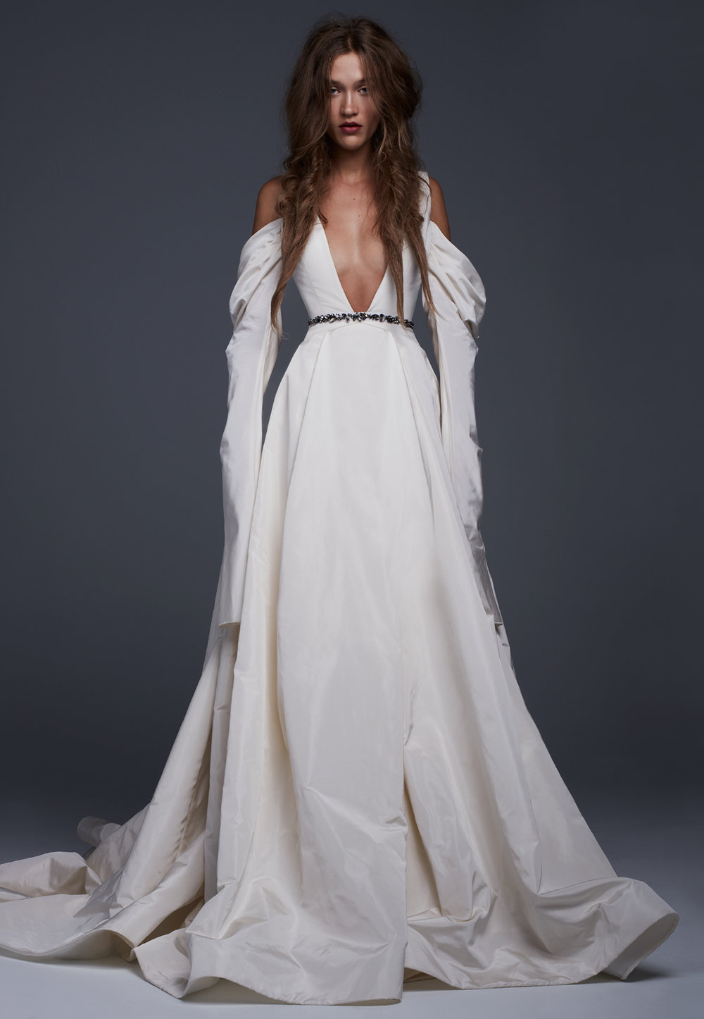 Season: Fall 2017    Gown name: Viviana    Description: A silk faille plunging V-neck gown with draped sleeves and jeweled belt detail.