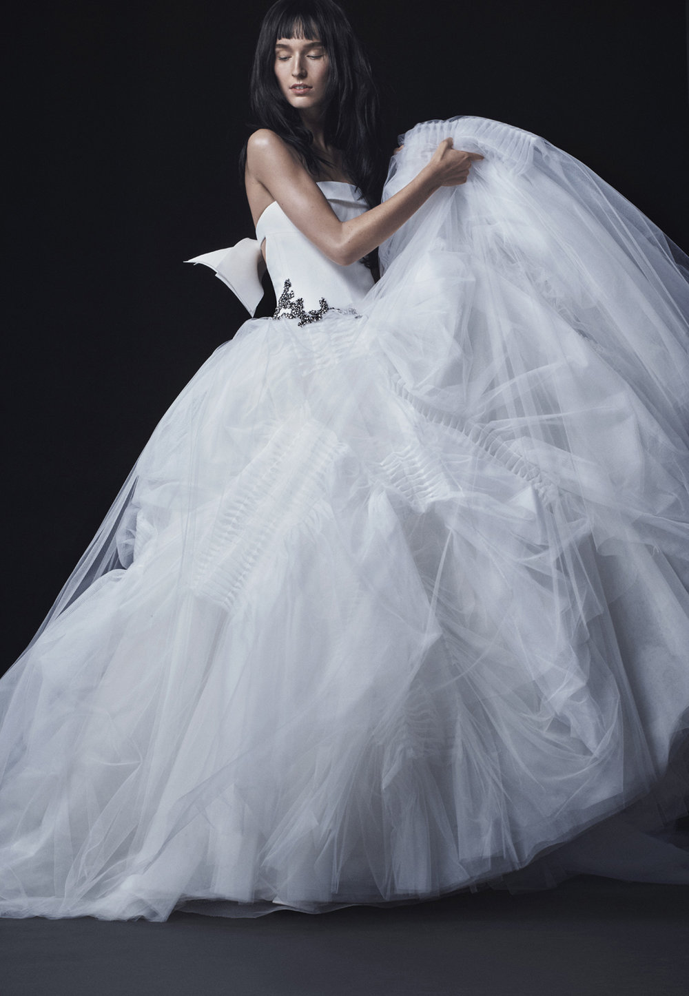 Season: Fall 2016    Gown name: Lola    Description: A soft white silk crepe strapless ball gown with dramatic pleated tulle skirt and crystal accent at the waist accented by a silk bow at the back.