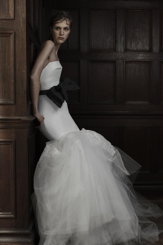 Season: Spring 2016    Gown name: Manuela 露肩領口美人魚裙形剪裁婚紗    Description: 露肩領口美人魚裙形剪裁婚紗,平口軟白綢在胸口打折,胸前形成一個別緻 的剪裁。褶皺的薄紗裙擺由人手親手縫製出立體效果,是非常細膩的作品。配上黑色蝴蝶 結腰帶就給晚禮服般動人。