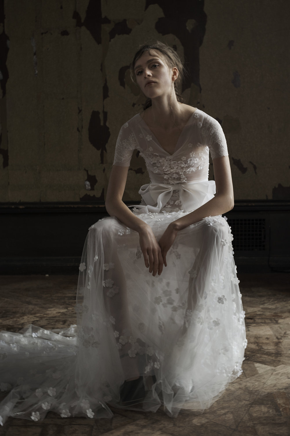 Season: Spring 2016    Gown name: Camilla    Description: A light ivory gathered stretch illusion short sleeve soft mermaid gown with French tulle skirt accented by hand applique silk flowers and hand pieced Chatilly lace.