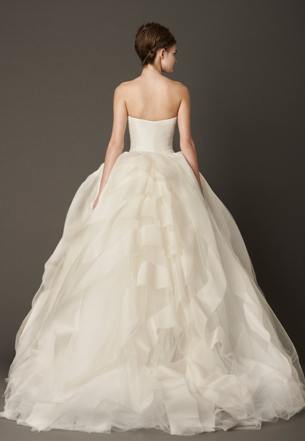 Iconic Style    Gown Name: Liesel    Description: A strapless ball gown with ribbon embroidered bodice and silk organza floating flange skirt accented by lace appliqué detail at hem. Available in white or ivory.