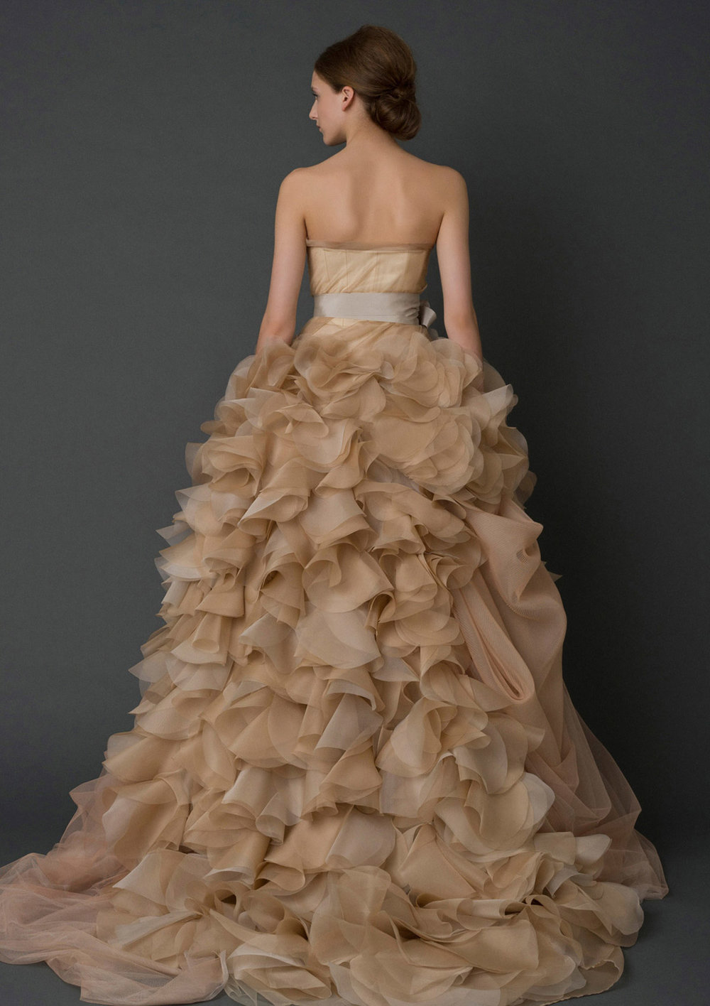 Iconic Style    Gown Name: Hayley    Description: A strapless soft ball gown with draped corset bodice and asymmetrically swept floating organza petal skirt with pleated tulle. Available in ivory and white, shown in nude and sand.