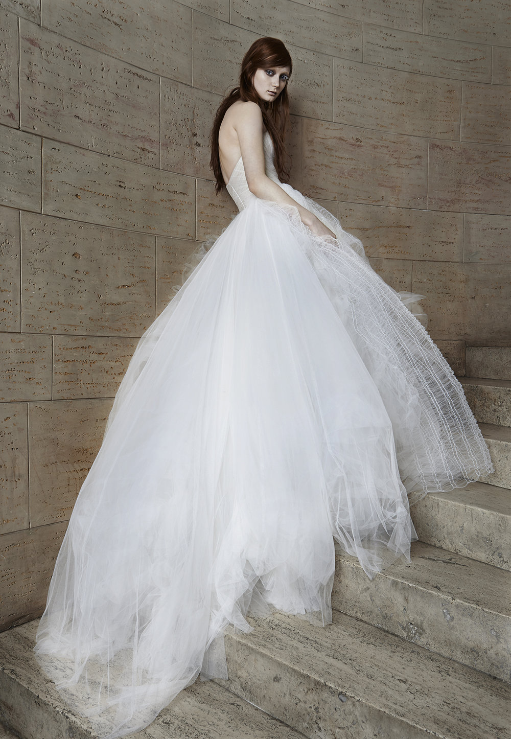 Iconic Style    Gown Name: Octavia 抹胸领口公主大裙剪裁的婚纱    Description: 抹胸领口公主大裙剪裁的婚纱,Octavia 是一袭充满了动态美感的婚纱,新 娘在行走中裙体仿佛被片片随意而轻盈的薄纱围绕。手工的薄纱抓折胸衣,无负担紧密的 贴紧身躯,营造纤细的腰身。不规则的薄纱,如蝉翼般轻柔,穿在身上一点也不嫌重。穿 着她的新娘可爱、柔软而自由,仿若云朵漂浮着被风带往任何地方。