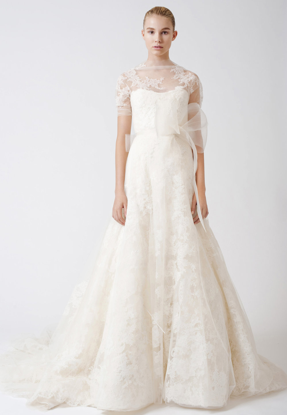 Iconic Style    Gown Name: Esther    Description: An Illusion sweetheart soft A-line gown with multi-layered Chantilly lace appliqué, sheer tulle elbow-length sleeve with floating lace, and horsehair sash at natural waist. Available in ivory or white with ivory or white horsehair bow.