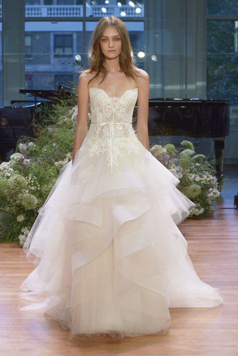 Season: Fall 2017    Gown name: Tresor    Description: A strapless sweetheart ball-gown with lace bodice and asymmetrical tiered skirt.