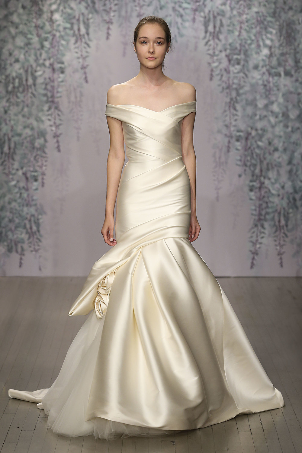 Season: Fall 2016    Gown name: Aubrey    Description: An off-shoulder modified trumpet gown with draped bodice and hand tufted skirt with rosette accents.