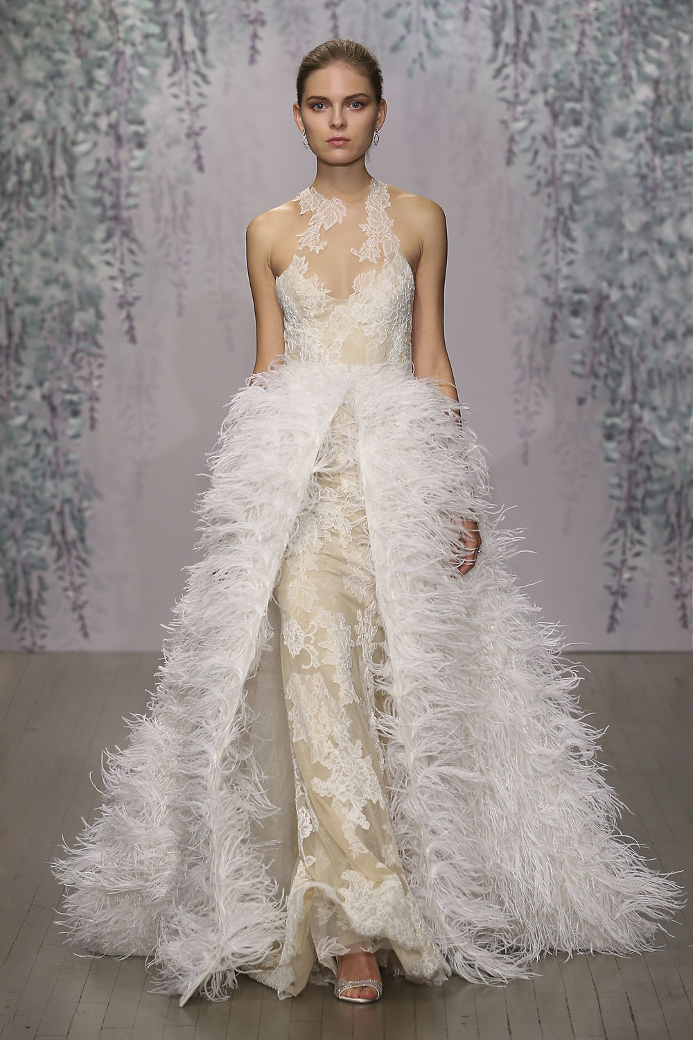 Season: Fall 2016     Gown name: Azelea    Description: A silk white and nude Chantilly and re-embroidered lace racer illusion neckline sheath with crisscross back