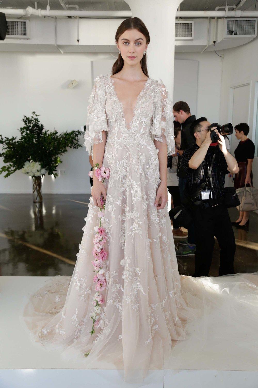 Season: Fall 2017    Gown name: Estrella    Description: A V-neck tulle gown with 3D floral threadwork and detachable cape.