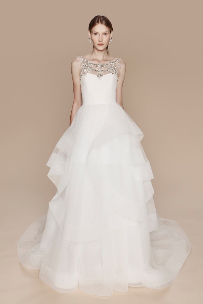 Season: Fall 2017    Gown name: Madison 船形領口A字裙形剪裁婚紗禮服    Description: 船形薄紗領口A字裙形剪裁婚紗,船形薄紗領部份飾上白水晶、銀水晶和貝 母寶石細節,閃石的光影反映讓新娘臉色更紅潤。上身採用垂褶設計,裙擺是不規則馬尾 扁帶,配合裙後身的大圓拖尾,富層次感又華麗。這婚紗的造型非常適合海灘婚禮。