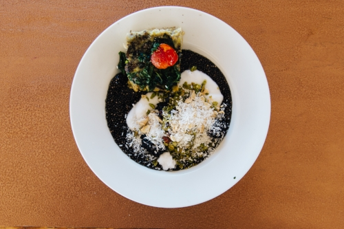 charcoal-chia-seed pudding with organic greek yogurt topped with matcha granola and shredded coconut served with cherry tomato, spinach and goats cheese