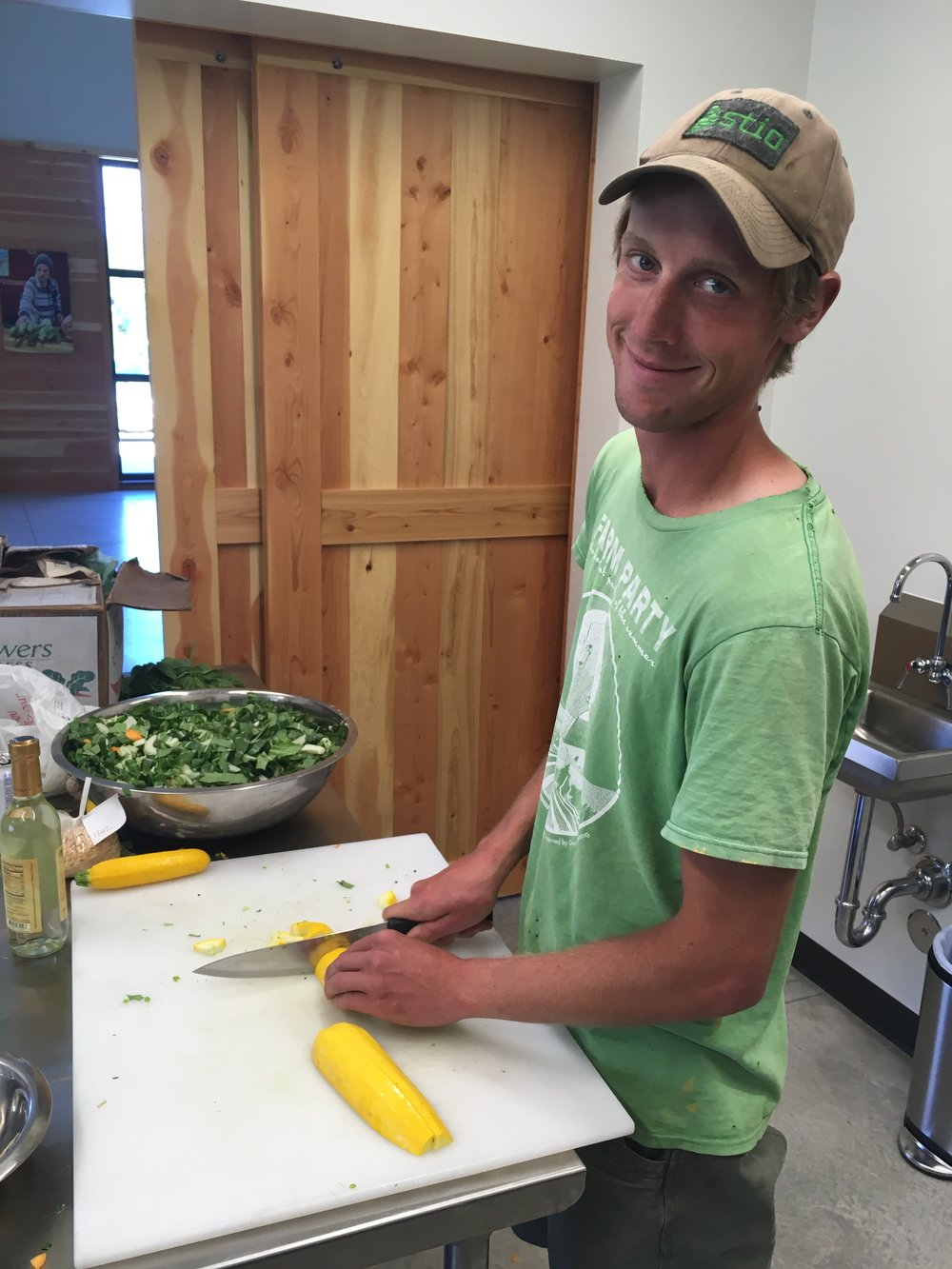 Patrick chopping summer squash with a smile at the River Road Farmstead.