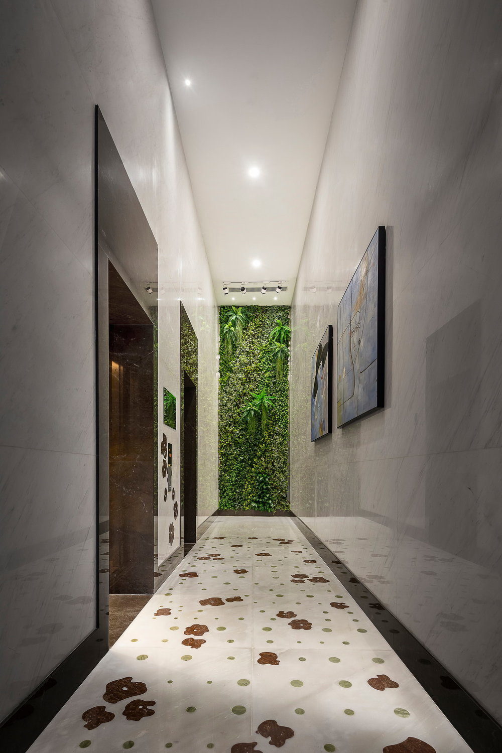 The floor is inlaid with marble flowers and the wall at the end of the corridor is made up entirely of plants