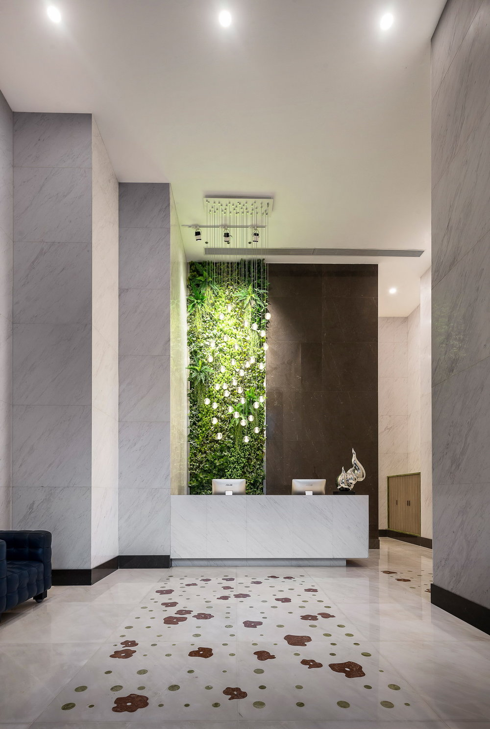 "Building front desk with the green wall behind and a ""rug"" of red marble flowers"
