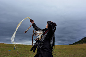 Picture of a novice shaman making a milk offering at her initiation near Ulaanbaatar, Mongolia