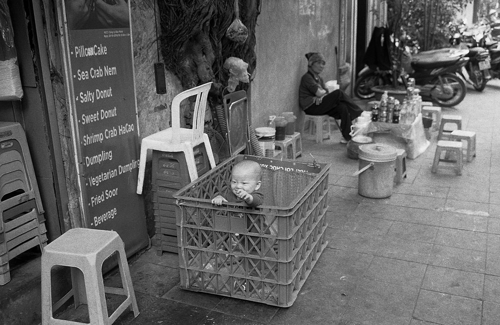Makeshift baby crib in the streets of Hanoi. Cute, happy baby.