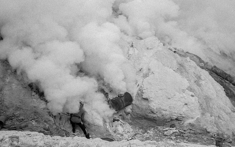 A sulfur miner appears minuscule against the enormous gas engulfing the landscape.